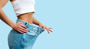 Weight loss. Woman in oversize jeans on pastel blue background. Diet concept and weight loss. Woman in oversize jeans on pastel blue background Stock Images