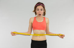 Weight loss woman shocked. Funny weight loss woman measuring her waist looking shocked on grey background Royalty Free Stock Image