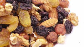Nuts and dried fruits in bulk. Weight of nutmixture in bulk on a white background stock footage