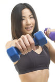 Weight out in front. A fit Asian woman holding out a free weight in her hand. Focused on foreground Royalty Free Stock Image