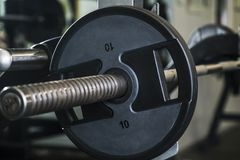 Weight plate on barbell in gym, fitness center royalty free stock photography