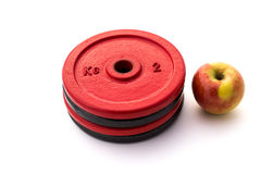 Weight Plates and Apple. White Background. Studio shot of weight plates and an apple on a white background Stock Photos