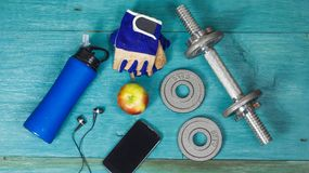 Weight plates, gloves and smartphone on wooden background Royalty Free Stock Image