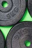 Weight plates on a green floor inside a weight training gym stock photo