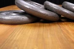Weight plates. A stack of weight plates on a wooden top table Royalty Free Stock Photos