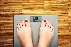 Weight problems concept suggested by woman stepping on a weight scale with the phrase `Oh my god!` Royalty Free Stock Photos