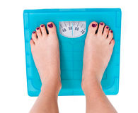 Weight Scale. Woman on weight scale on isolated background royalty free stock photo