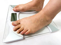 On the weight scale. Woman on the weight scale royalty free stock images