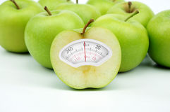 Weight scale made of green apple on white background stock photos