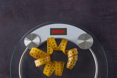 Weight scale with a measuring tape. Concept- lifestyle, sports a. Nd diet for weight loss. Copy space. On the measuring scale written word - HELP royalty free stock photos