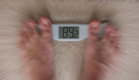 Weight scale panic. Blur on weight scale and feet. focus on numbers royalty free stock photos