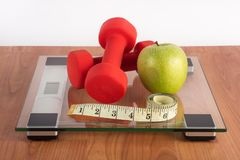 Weight scale with red dumbbell, measuring tape and fresh green apple on wooden floor stock photography