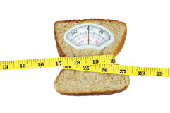 Weight scale with slice of bread and measuring tape on white bac. Weight scale with wholesome slice of bread and measuring tape isolated on white background royalty free stock photo