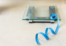 Weight scale and tape measure on bathroom Royalty Free Stock Photo