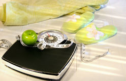 Weight scale on tile floor with towel and slippers stock photo