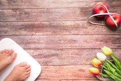 Weight scale white digital with women feet standing on scale and diet red apple bind with measuring tape on the wooden backgrounds. Health and fitness life royalty free stock photography