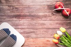 Weight scale white digital with women feet standing on scale and diet red apple bind with measuring tape on the wooden backgrounds. Health and fitness life stock photo