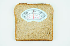 Weight scale with wholesome slice of bread on white background. Weight scale with wholesome slice of bread isolated on white background Stock Image