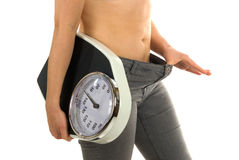 Weight Scale. A woman lost a lot of kilo's and does not fit in her trousers anymore Stock Photography