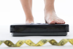 Weight scale. Woman measure weightloss with isolated whie background royalty free stock photography