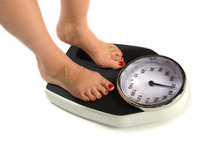 Weight Scale. A woman is standing on a weight scale royalty free stock photos