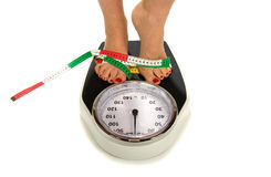 Weight Scale. A woman is standing on a weight scale with measuring tape Royalty Free Stock Photography
