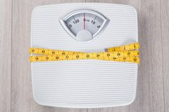 Weight scale wrapped in measure tape Stock Photo
