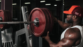 Weight training African doing bodybuilding. In gym Royalty Free Stock Photography