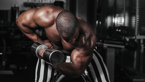 Weight training African doing bodybuilding. In gym Stock Images