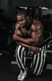Weight training African doing bodybuilding. In gym Royalty Free Stock Image