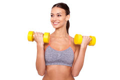 Weight training. Beautiful young sporty woman in tank top exercising with dumbbells and smiling while standing against white background Stock Photos