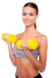 Weight training. Beautiful young sporty woman in tank top exercising with dumbbells and smiling while standing against white background Royalty Free Stock Images