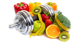 Weight Training. Chrome dumbbells surrounded with healthy fruits and vegetables studio shot on a white background with shadows Royalty Free Stock Photos