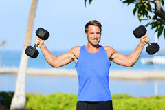 Weight training Fitness man with dumbbell weights. In workout outside. Fit muscular male lifting weights in shoulder press exercise. Sports model exercising Stock Photography