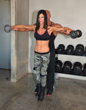 Weight Training. Trainer helps client train with weights. Couple training together Royalty Free Stock Photos