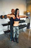 Weight Training. Trainer helps client train with weights. Couple training together Royalty Free Stock Photo