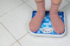 Weight woman standing on a retro style weighing machine Stock Images
