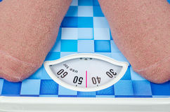Weight woman standing on a retro style weighing machine Royalty Free Stock Image