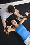 Weight workout. Man assisting woman lifting weights at gym Stock Photography