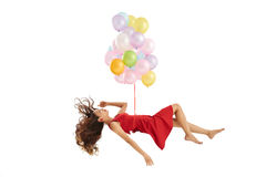 Weightless woman. Sleeping Vietnamese woman lifted up by bunch of balloons,  on white Stock Images
