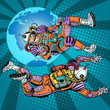 Weightlessness astronauts in space over the earth. Pop art retro style. The study of space. Retro astronauts vector. Command of a spaceship Stock Photos