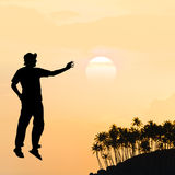 Weightlessness. Male silhouette on background amazing sunset Stock Photo