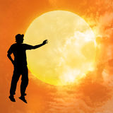 Weightlessness. Male silhouette on background amazing sunset Stock Image