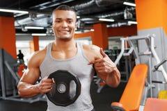 Weightlifter που δείχνει σε δίσκο βάρους Στοκ Φωτογραφία