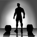 Weightlifter with barbell silhouette. Weightlifter with bar before exercise Royalty Free Stock Photos