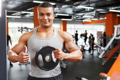 Weightlifter holding disk with thumbs up Royalty Free Stock Image