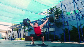 Weightlifter Is Pulling The Barbell Above His Head Stock Photo