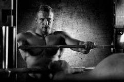 The weightlifter keeps his hands on the barbell and looks at him. Self in the mirror. Reflection in the Mirror Stock Images