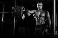 The weightlifter leans his hand on the barbell and looks menacin. Gly forward. Front view Royalty Free Stock Image