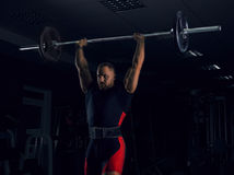 Weightlifter lifts the bar above his head. Strength training with a huge weight Stock Photos